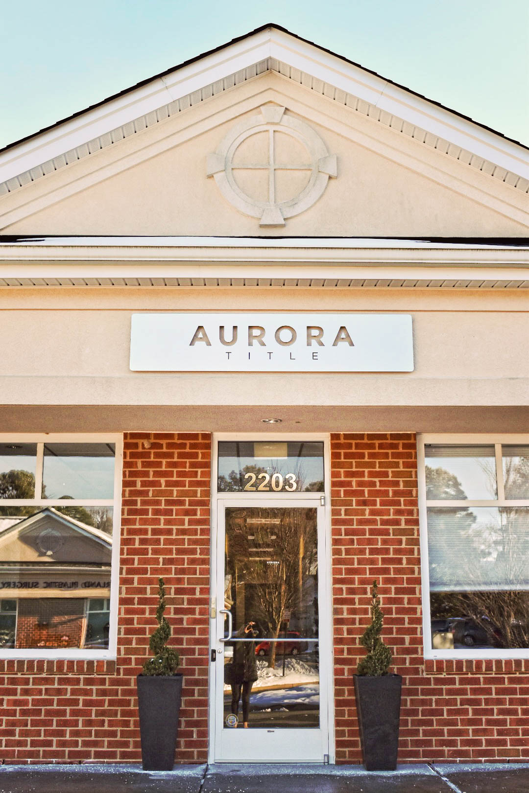 metal exterior sign that says Aurora Title on a brick building