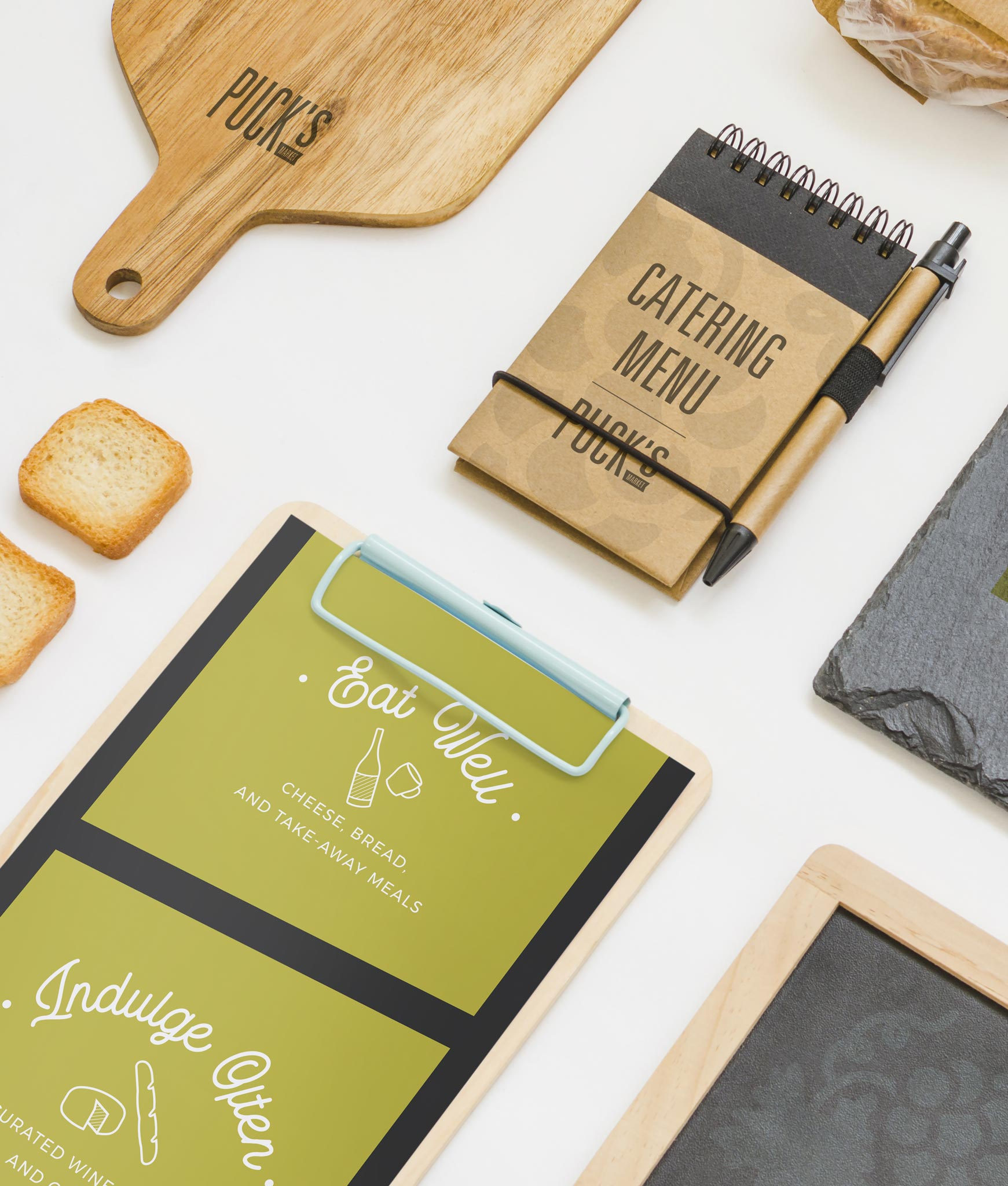cutting board, menu, and clipboard branded for Puck's Market