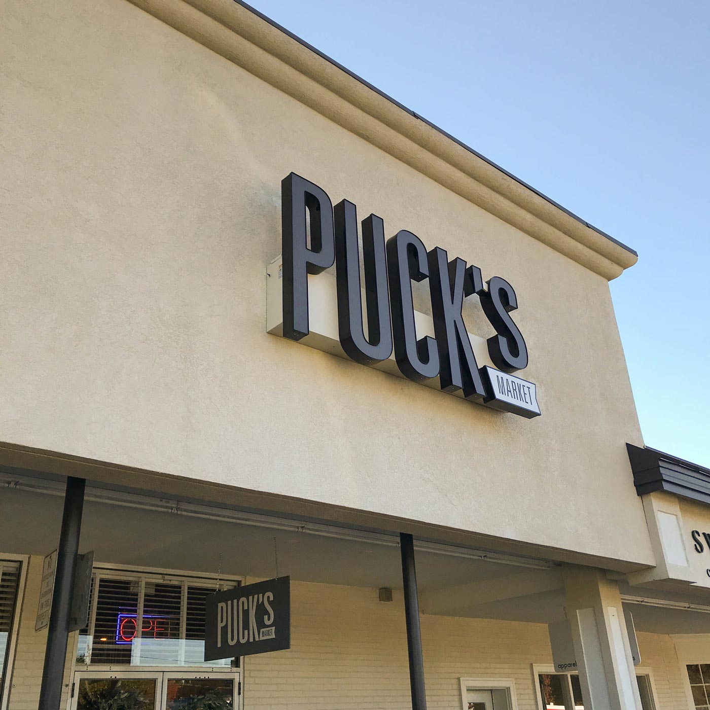 exterior sign that says Puck's Market on tan building